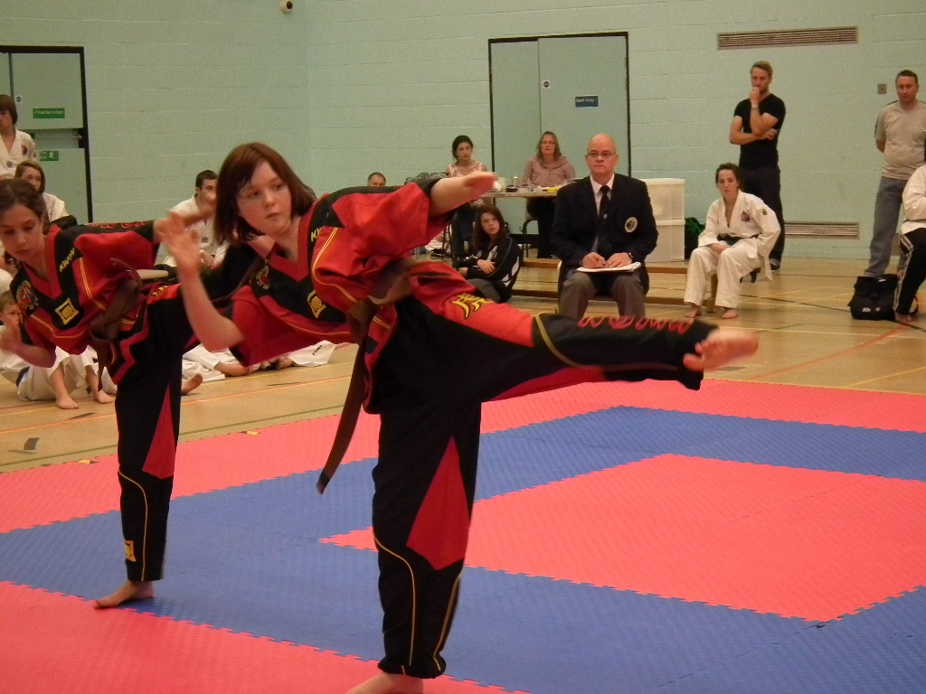 Young female taekwondo student demonstrating a side kick