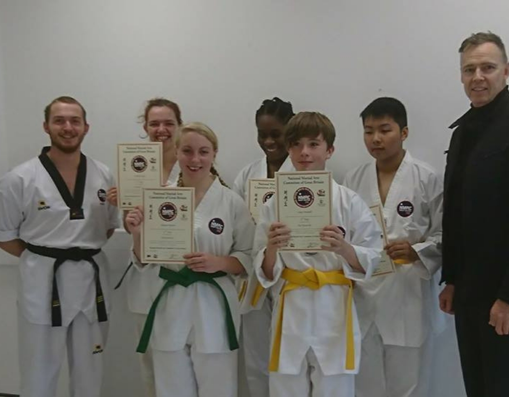 Successful Strikers students smiling and holding grading certificates in Portsmouth