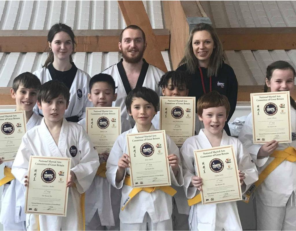 Taekwondo kids yellow belt candidates holding grading certificates